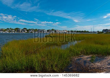 Green marsh grass lines an inlet under a blue sky and white clouds