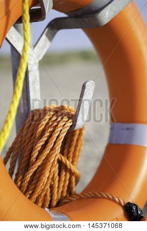 Life saver buoyancy aid with orange nylon rope on metal stand. Focus is on rope in foreground.