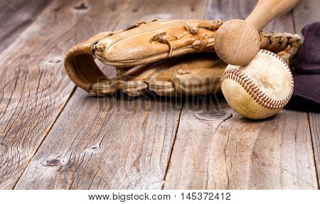 Old baseball equipment on rustic wooden boards. Selective focus on bat handle and ball.