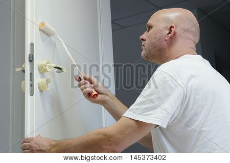 Craftsmen during the painting of a door in an office building