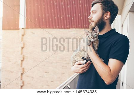 Beautiful man is holding and hugging cute Devon Rex cat. Happy young man is standing on a balcony with his cat. Home pets, Lifestyle. Curiosity expression