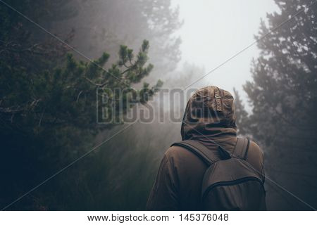 Man is walking in foggy forest. Traveler with backpack. It is easy to get lost, bad view in a forest
