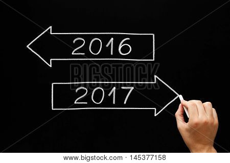 Hand drawing New Year concept with white chalk on blackboard. Going ahead to year 2017 and leaving the year 2016 behind.