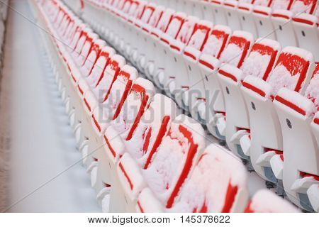 Rows of red empty seats of grandstands covered by snow on stadium