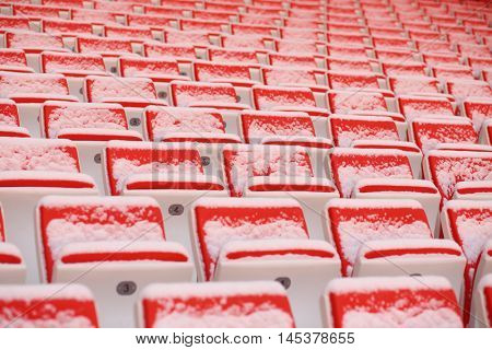 Rows of bright empty seats of grandstands covered by snow on stadium