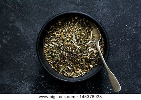 Organic herbal tea in a bowl with silver spoon