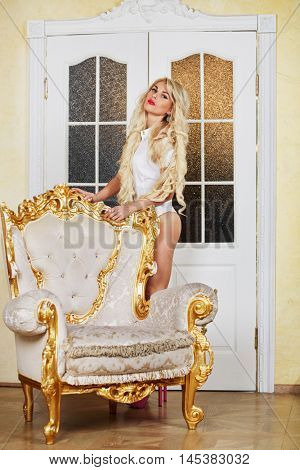 Young blonde woman stands next to the vintage gilt armchair.