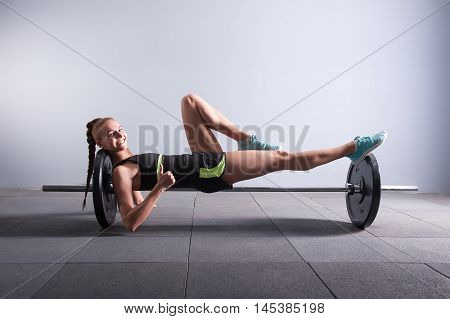 fitness, sport, exercising hard working concept - smiling young woman on the barbel showing thumbs up in gym