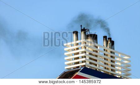 Naval maritime sea concept. Vessel chimneys releasing smoke. Ship part blue sky background.