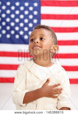 Boy in front of American flag with hand over heart
