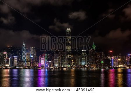 Hong Kong Harbor skyscrapes late into the evening with colored lights reflecting off the bay and clouds encircling the moutains and sky.