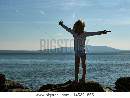 boy on the beach. he stands on the rocks. Bulgaria Burgas