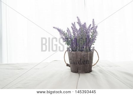 The bed with purple lavender flower and sunlight from glass of windows in bedroom High key picture style.