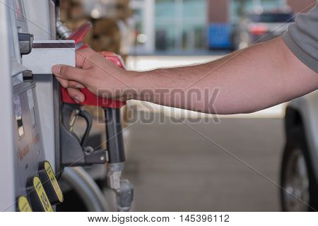 Male using credit card at the gas pump, fuel prices going up and down.