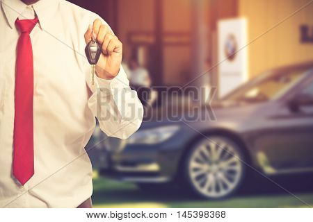 Car Salesman Handing Over The Keys For A New Car On Background.vintage Color