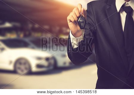 Businessman Showing A Car Key - Car Sale & Rental Business Concept.vintage Color