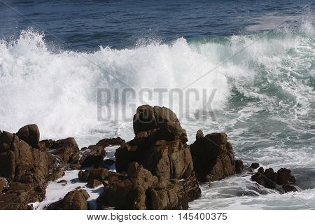This is an image of rocks and waives at Asilomar State Preserve in Pacific Grove, California.