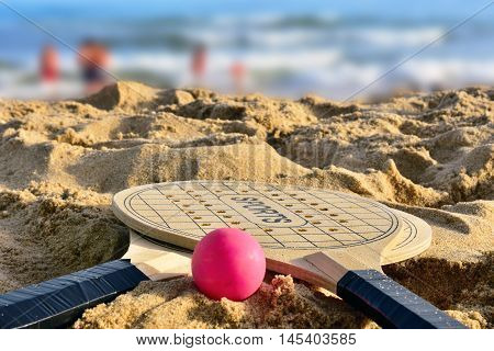 Two raquets and ball on the sand beach. End of summer