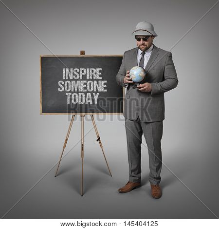 Inspire someone today text text on blackboard with businessman and globe