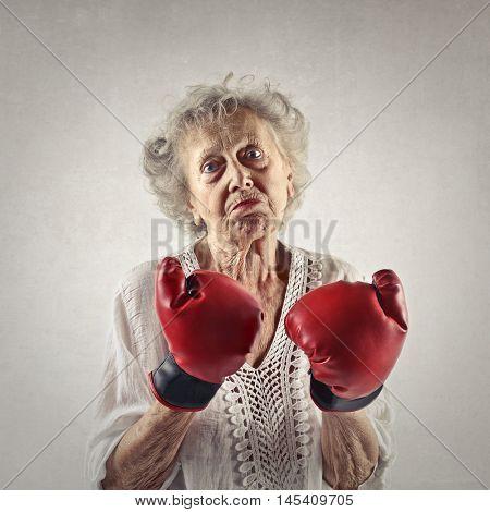 Elderly woman wearing boxing gloves