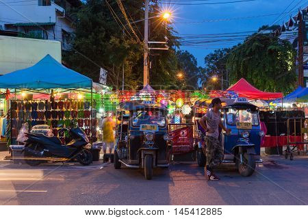 CHIANG MAI THAILAND - AUGUST 21: Tuk-tuk taxis wait for customers near Saturday Night Market on August 21 2016 in Chiang Mai Thailand.