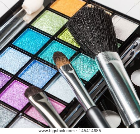 Make-up colorful eyeshadow palettes with makeup brushes. Focus on the black makeup brushes. Shallow depth of field