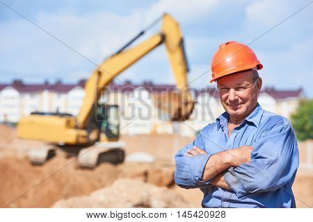 construction worker driver in front of excavator loader