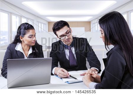 Three young businesspeople looking at employment contract with laptop on the table shot in the office