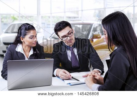 Portrait of two young car sellers showing a credit contract for new car on their buyer in the showroom