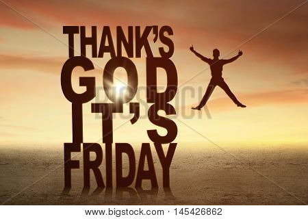 Silhouette of cheerful businessman jumping next to text Thanks GOD it's Friday