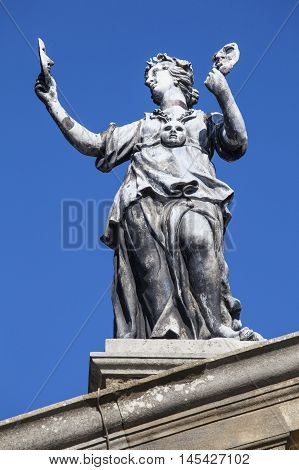 An old statue of an actor holding masks on top of the Clarendon Building in the historic city of Oxford England. The building is situated next to the Sheldonian Theatre.