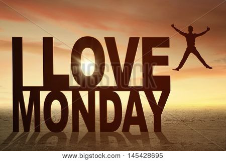Silhouette of happy businessman jumping next to word I love Monday shot in the morning