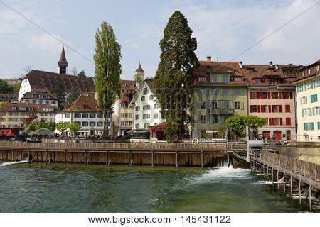 LUCERNE SWITZERLAND - MAY 02 2016: Colorful buildings down by the river Reuss shows the unique character of the city and variety of sightseeing attractions. The town is a destination for many travelers