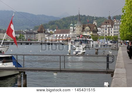 Lucerne Switzerland - May 02 2016: The city as seen from the Lake Lucerne. The octagonal stone tower which is one of the most recognizable landmarks in the city that can be seen from a far distance. Panorama of the city shows unique character and diversit