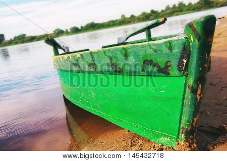 old wooden boat on the shore. old fishing boat with oars painted green on a sandy beach