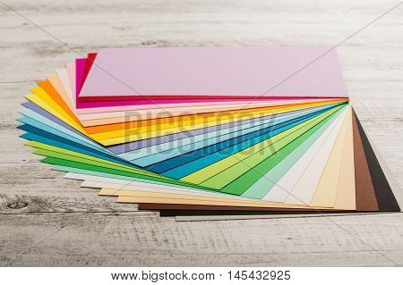 Sheets of colored paper, iridescent palette of colored paper, rainbow colors,  on the wooden table