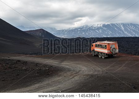 KAMCHATKA PENINSULA RUSSIA - JUNE 24 2016: Russian expedition truck KamAZ (6-wheel drive) on mountain road on background of lava fields and volcanoes. Eurasia Far East Russia Kamchatka Region Klyuchevskaya Group of Volcanoes.