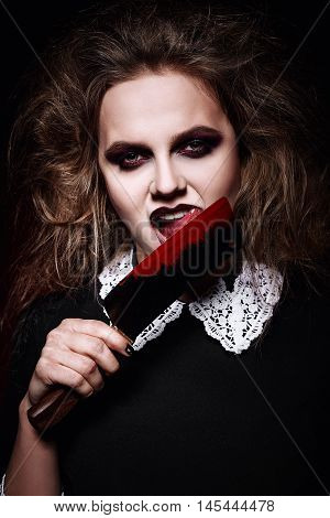 Horror shot: a scary evil girl licking bloody knife
