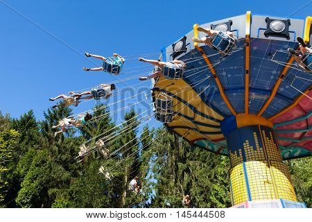 Biddinghuizen, The Netherlands - August 24, 2016: High speed carousel with park visitors during a ride at Walibi theme park.