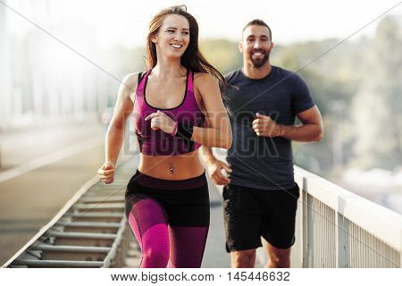 Happy couple running outdoors. People jogging together living healthy lifestyle.