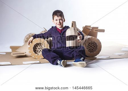 photo of young racer on a cardboar racing car.