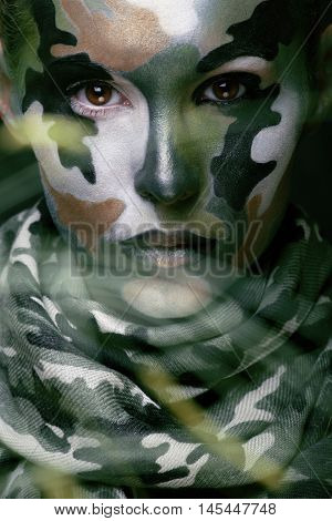 Beautiful young fashion woman with military style clothing and face paint make-up, khaki colors, halloween celebration close up, green pattern all over body