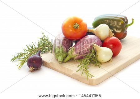 Summer veggies tomates, eggplants, Onion on wooden cutting board isolated on white