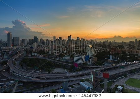 Sunset over cityscape downtown and highway interchanged