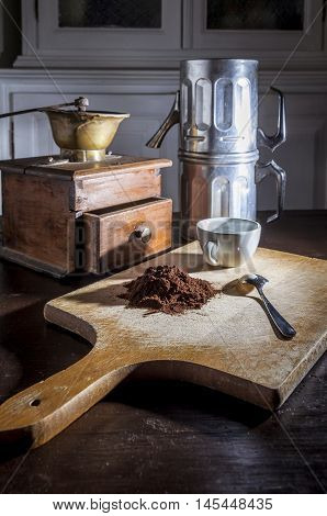 still life with a coffee mill a a neapolitan coffee moka and a white cup and steel little spoon beside a pile of coffe powder