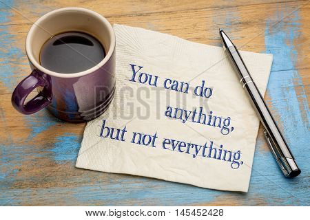 You can do anything, but not everything - handwriting on a napkin with a cup of espresso coffee