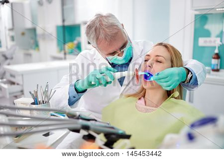 Dentist use dental light instrument for working with teeth