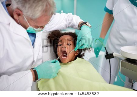 Male senior dentist repairing black kid's tooth