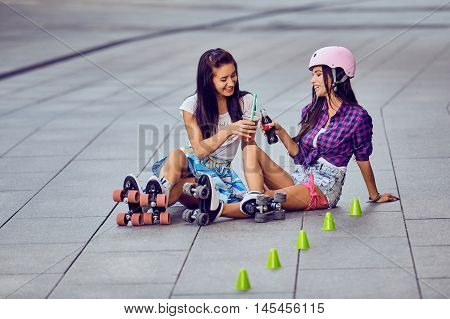 Two girls on roller skates resting and drinking lemonade. Happy women on the roller-skate in the urban park sitting on street a sunny day. Active lifestyle outdoors during sunset.