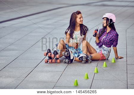 Young girls in skate park with roller skates and lemonade having fun sitting on street a sunny day. Two beautiful young girls on the floor resting after resting. Active lifestyle outdoors during sunset.
